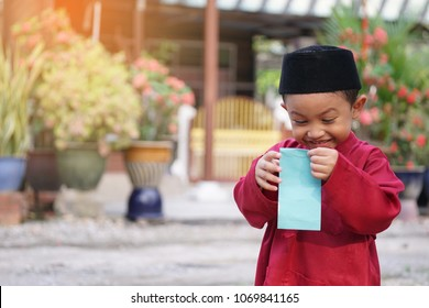 A Malay boy in Malay traditional cloth showing his happy reaction after received money pocket during Hari Raya celebration. On the money pocket written with Selamat Hari Raya or Happy New Year.