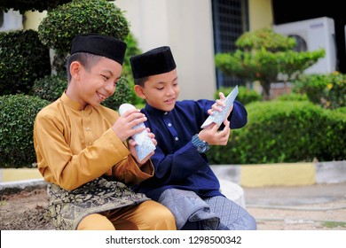 The Malay boys wearing Malay traditional cloth or Baju Melayu showing their happiness reaction after received money pocket during Eid Fitri or Hari Raya celebration.