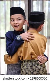 The Malay boys wearing Malay traditional cloth or Baju Melayu asking forgiveness.  Eid Fitr, Happiness & Forgiveness Concept.