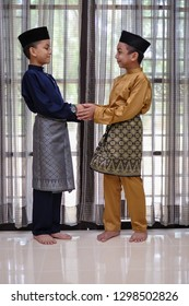The Malay boys wearing Malay traditional cloth or Baju Melayu asking forgiveness.  Eid Fitr, Happiness & Forgiveness Concept.