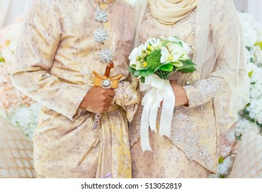 malay couple wedding.  Typically the bridegroom holds the kris and the bride holds flowers