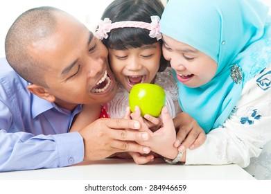 Malay family eating apple