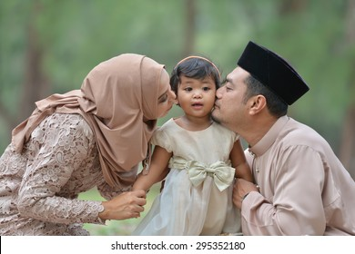 malay family having fun in the park ,malaysian people. Mother and father kissing his daughter.