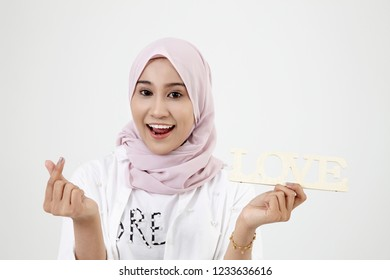 Malay girl with hand forming a heart shape, standing isolated on white background.