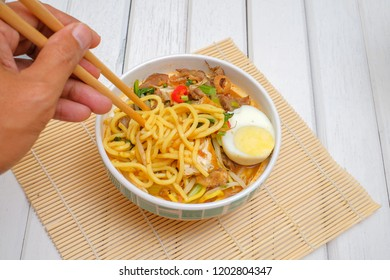 Malay Mee Rebus in the bowl  with chopsticks on white table This dish is made of noodles ,vegetable,egg with a spicy .