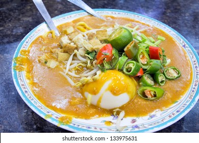 Malay Mee Rebus Noodle Dish Garnished with Cut Chili Peppers Tofu Chinese Celery and Hard Boiled Egg