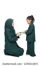 Malay mother giving money packet to daughter during festive celebration