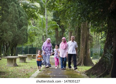 malay muslim family having fun walking in the park