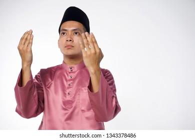 Malay Muslim man praying. Isolated on white background