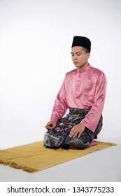 Malay Muslim man praying on a praying carpet. Isolated on white background