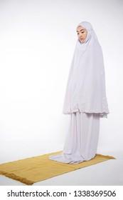 Malay Muslim woman praying on a praying carpet. Isolated on white background