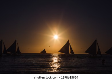 Malay, Philippines - January 12, 2016: one outrigger sailboat sailing on the horizon during the sunset in Boracay island, Malay city, Philippines.