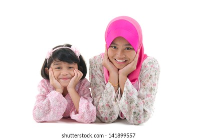 malay sisters laying on the floor with isolated white background