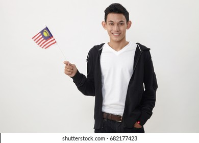 malay teenage holding a small malaysia flag