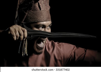 A Malay warrior with his keris ready for a duel in a traditional malay warrior costume isolated on black background