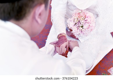 Malay Wedding Couple Putting A Gold Bracelet On Hand.Soft Focus And Shallow Depth Of Field.