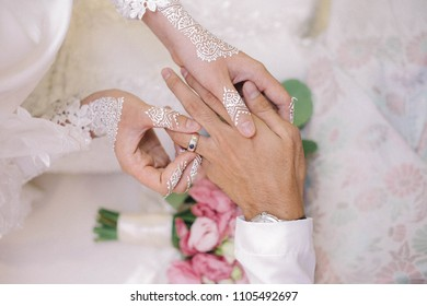 Malay Wedding Couple Putting A Ring On Hand