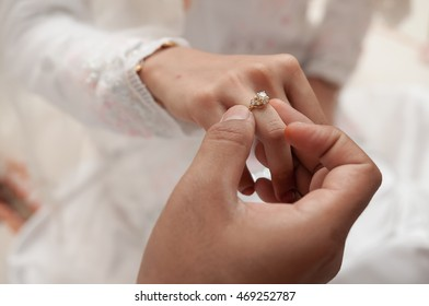 malay wedding groom bolstering gold ring on bride's finger. selective focus