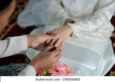 malay wedding in malaysia shows the man puts the ring on his beloved wife