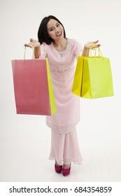 malay woman with baju kurung shopping for raya