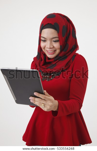 malay woman with red tudung using smart gadget