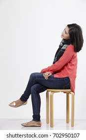 malay woman sitting on the stool on the white background