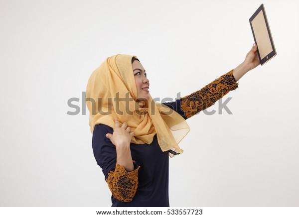 malay woman with tudung having fun with dummy ipad