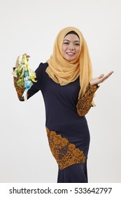 malay woman with tudung holding a bunch of ketupat