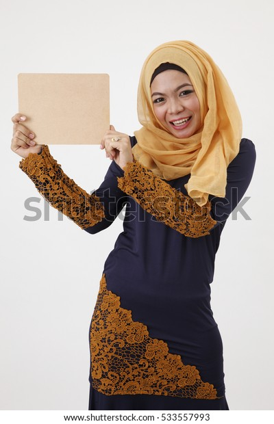 malay woman with tudung showing blank wooden board