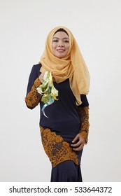 malay woman with tudung showing a bunch of ketupat