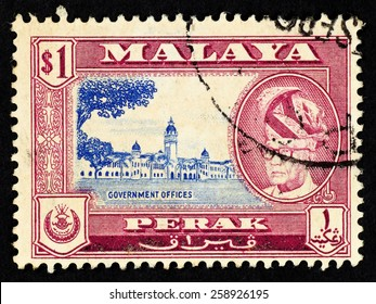 MALAYA - CIRCA 1957: Red color postage stamp printed in Perak (Federation of Malaya) with illustrative mage of government office building and portrait of Sultan Yussuf Izzuddin Shah.