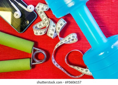 Malaysia, 2017 - Lay Flat - Dumbbell, Measuring Tape, Hand Grip, Mineral Water, Fresh Apple, Smartphone & Earphone on red background - Fitness Concept