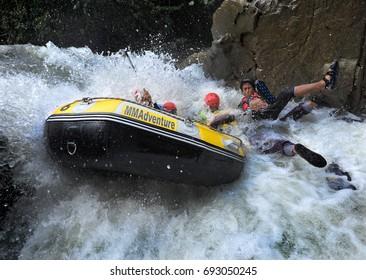 Malaysia, 30 Jun 2012 - Water rafting participants upside down in rapids at Sungkai River, 200km from Kuala Lumpur.