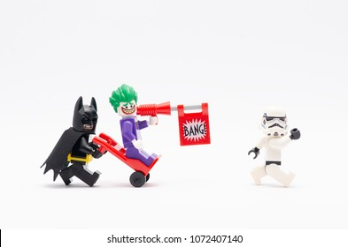 MALAYSIA, April 14, 2018. mini figure of batman pushing trolley with joker standing on it chasing storm trooper. Lego minifigures are manufactured by The Lego Group.