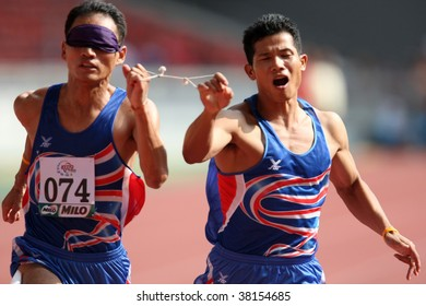 MALAYSIA - AUGUST 15: Thailand's blind athlete Kitsana Jorchuy runs with a guide at the track and field event of the fifth ASEAN Para Games on August 15, 2009 in Kuala Lumpur, Malaysia.
