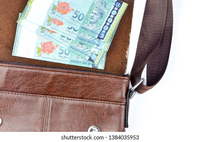 Malaysia bank note with sling bag on white background.