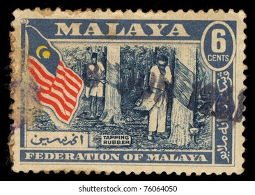 MALAYSIA - CIRCA 1961: A stamp printed in Malaysia shows image of people tapping rubber, circa 1961