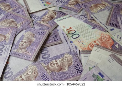 Malaysia Currency (MYR): Stack of Ringgit Malaysia bank note. There is a hundred ringgit malaysia scattered on the table.