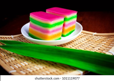 Malaysia dessert, Kuih Lapis or colorful glutinous rice layer cake in white dish with pandan leaves on table background