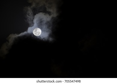 MALAYSIA - FEBRUARY 5, 2015: Moon behind the clouds. This photo was taken during a dark cloudy night sky with bright full moon behind them.