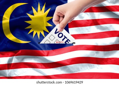 Malaysia general election concept. close up hand of a person casting a ballot at elections during voting on canvas Malaysia flag background.