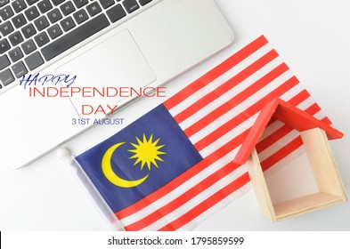Malaysia Independence day concept. Laptop and toy house with Malaysia flag and text Happy Independence Day 31st August also known as Hari Merdeka. Selective focus.