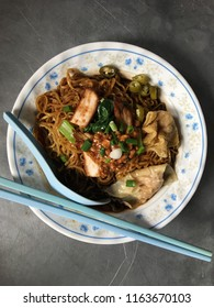 Malaysia infamous street food wanton mee. Wanton dumpling is mixture of pork and prawn wrapped in skin make with flour powder. The brown color sauce is from oyster sauce dressing.