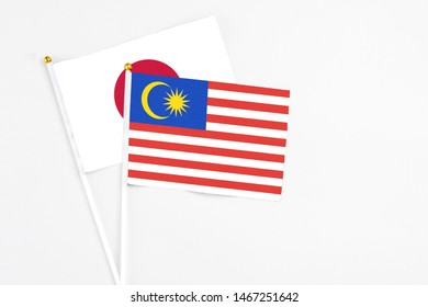 Malaysia and Japan stick flags on white background. High quality fabric, miniature national flag. Peaceful global concept.White floor for copy space.