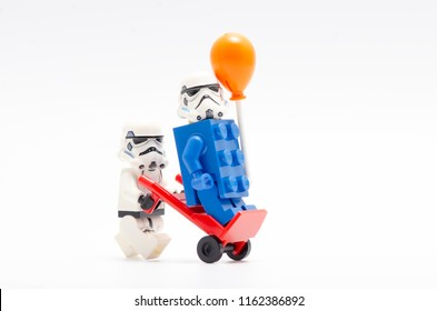 MALAYSIA, jul 30, 2018. Lego storm troopers pushing trolley with one of them on trolley wearing blue brick holding a balloon . Lego minifigures are manufactured by The Lego Group.