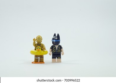 malaysia, july 22, 2017. lego c3p0 robot wearing bobbin' floatie ring and flippers and vacation batman . Lego minifigures are manufactured by The Lego Group.