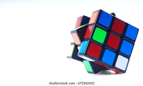 Malaysia, July 8 2017- Colourful Rubik's cubes on white background. Solving difficult IQ quiz tasks. Selective focus and crop segment.