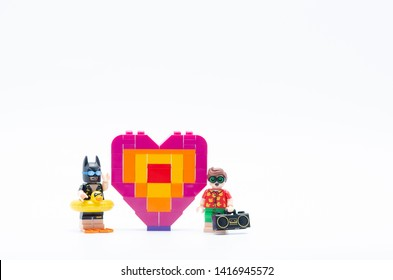 Malaysia, june 02, 2019. lego batman with robin and piece offering heart shape.  Lego minifigures are manufactured by The Lego.