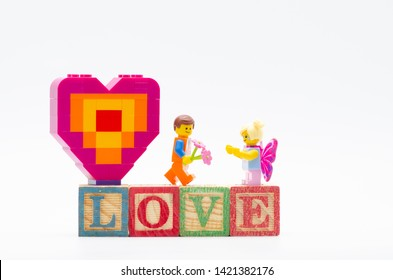 Malaysia, june 02, 2019. lego emmet giving flower to butterfly girl and piece offering heart shape.  Lego minifigures are manufactured by The Lego.