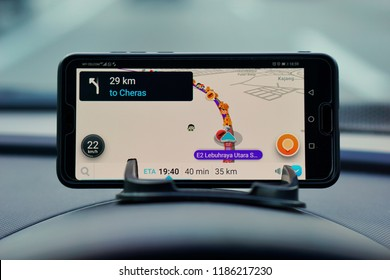 MALAYSIA, Kuala Lumpur, August 26, 2018: The Waze application on smartphones shows the road on the car dashboard with a blurred background.